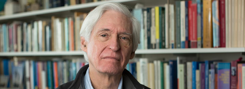 Prof John Bowers sitting in front of full bookshelves