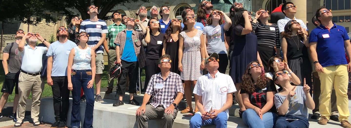 Linguistics faculty and students wearing eclipse glasses and watching 2017 solar eclipse