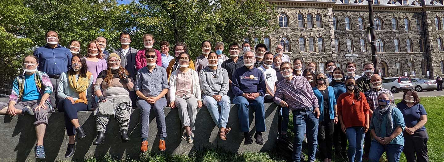 Linguistics Dept facult, students, and staff in front of Morrill Hall wearing clear masks