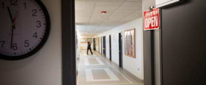 Hallway and door with We're Open sign