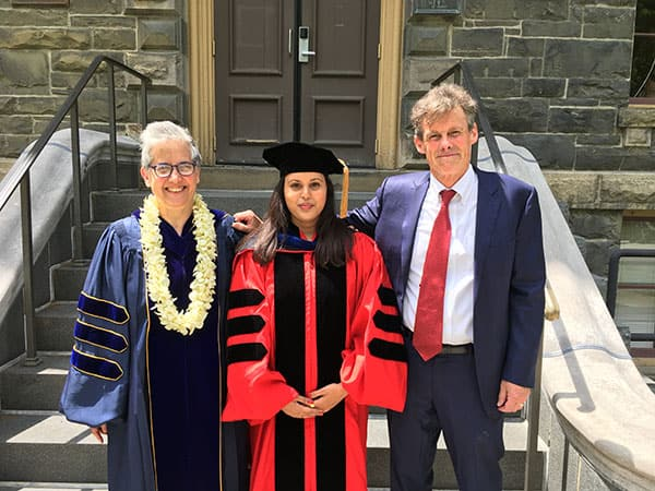 Abby Cohn, Shohini Bhattasali, and John Whitman pose in front of Morrill Hall on Commencement Day